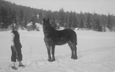 Eva Norin med hästen Svarten i ett vinterlandskap. Foto i privat ägo.
