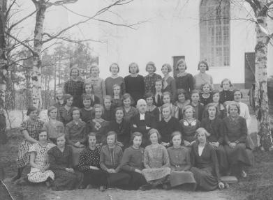 Gruppbild av konfirmander tagen utanför Järvsö kyrka med prästen i mitten. Eva sittandes som nummer två från höger längst fram. Foto i privat ägo.