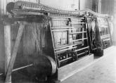 Maskin för linberedning vid linspinneriet i Forsa socken år 1925. Källa: Foto taget av Undéns Fotografiatelier, fotot ägs av Tekniska museet Gävleborg. Tillgängligt: https://digitaltmuseum.se/021016319575/linspinneri-i-lund-i-forssa-socken-i-halsingland, [180125]. Inga bearbetningar.