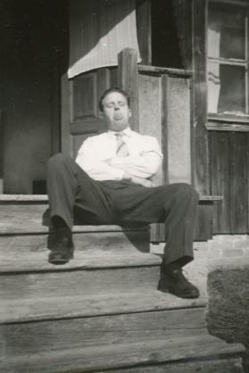 Erling sittandes i solen på förstukvisten till gården Rönnåsen. Uppenbart är han full i bus som lipar åt fotografen.